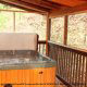 Porch View with Hot Tub of Cabin 262 (Tucked Away) at Eagles Ridge Resort at Pigeon Forge, Tennessee.