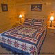 Bedroom with Two Night Stands in Cabin 860 (Cozy Bear Overlook) at Eagles Ridge Resort at Pigeon Forge, Tennessee.