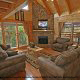 Living room with vaulted ceiling and fireplace in cabin 864 (The Cedars) at Eagles Ridge Resort at Pigeon Forge, Tennessee.