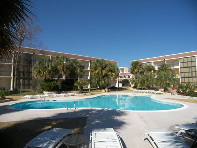 Outdoor Pool View With Chaise Lounge Chairs At The Ocean Vacation Villas In Biloxi