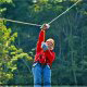Lady with red sweatshirt enjoying a ride at zipline adventures in Pigeon Forge Tennessee.